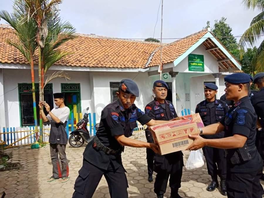 Anggota Brimob Detasemen B Pelopor Polda Banten Sedang Memberikan Bantuan ke Yayasan Karya Asih